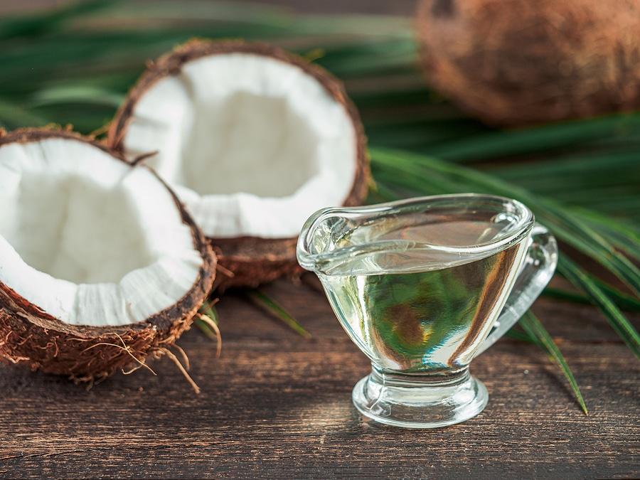split open coconut next to a small jug of MCT Oil being taken on an empty stomach