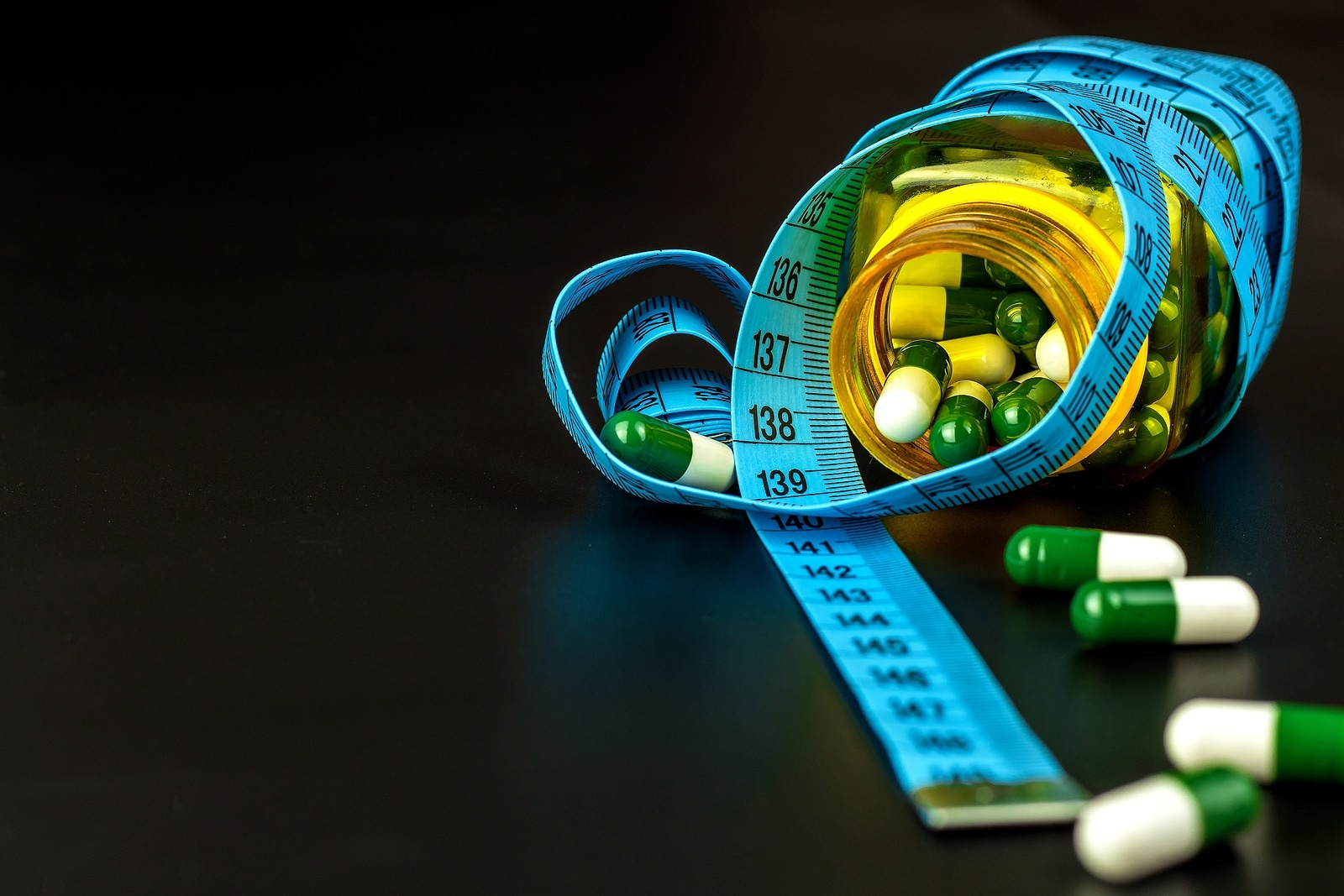 Pills With Measuring Tape. Weight Loss Concept.
